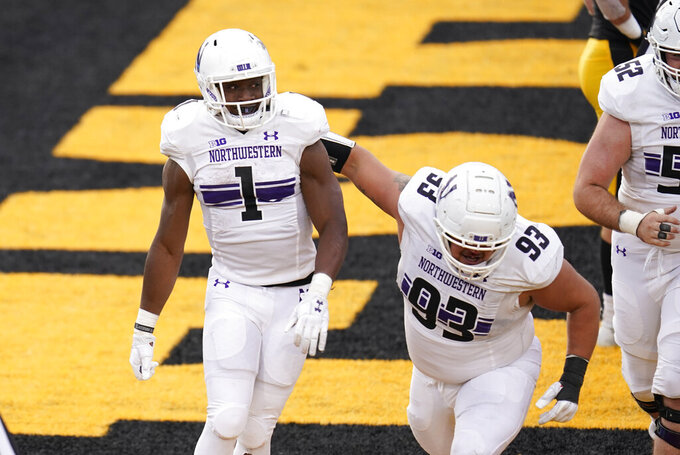 Northwestern running back Jesse Brown (1) celebrates with teammate Northwestern Joe Spivak (93) after scoring on a 2-yard touchdown run during the second half of an NCAA college football game against Iowa, Saturday, Oct. 31, 2020, in Iowa City, Iowa. (AP Photo/Charlie Neibergall)