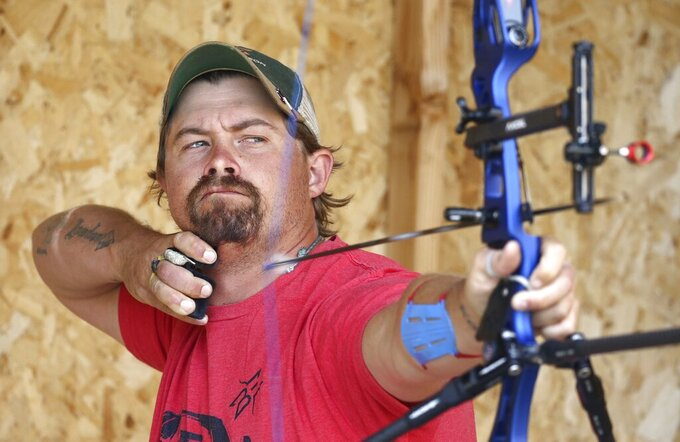 FILE - U.S. Olympic Team archer Brady Ellison lets an arrow fly as he practices on his range in Miami, Ariz., in this Thursday, April 30, 2020, file photo. Ellison is the top-ranked archer in the the world and the favorite at the Tokyo Games. A few years ago, he wasn't sure if he would even shoot another arrow again. (AP Photo/Ross D. Franklin, File)