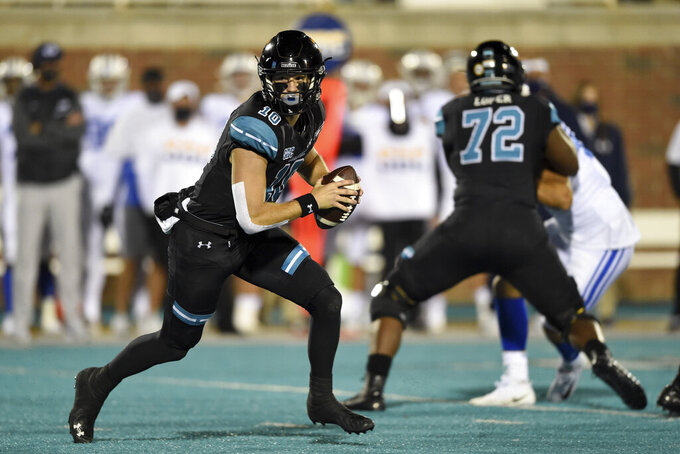 Coastal Carolina quarterback Grayson McCall, left, scrambles during the first half of an NCAA college football game against BYU, Saturday, Dec. 5, 2020, in Conway, S.C. (AP Photo/Richard Shiro)