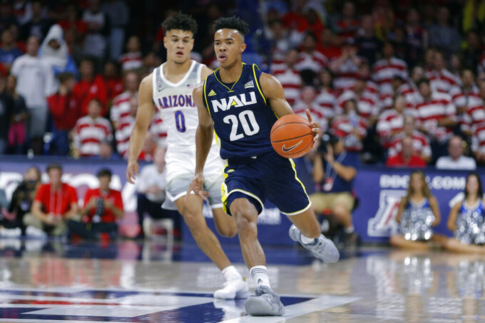 Northern Arizona guard Cameron Shelton (20) drives past Arizona guard Josh Green during the first half of an NCAA college basketball game Wednesday, Nov. 6, 2019, in Tucson, Ariz. (AP Photo/Rick Scuteri)