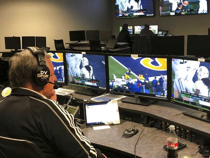 David Warden, the Big 12's replay coordinator, reviews a play from the West Virginia-Baylor NCAA college football game in the conference's centralized replay center in Irving, Texas, Thursday, Oct. 25, 2018. In the background at rear left, at one of the centers six game stations, is the two-man crew assigned specifically to cover the Baylor-West Virginia NCAA college football game. (AP Photo/Stephen Hawkins)