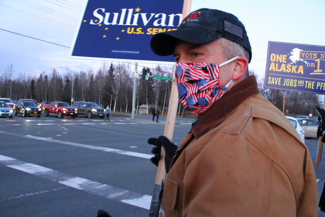 FILE - In this Nov. 2, 2020, file photo, Republican U.S. Sen. Dan Sullivan waves a sign at a busy intersection in Anchorage, Alaska. Sen. Sullivan on Wednesday, Nov. 11, 2020, won re-election in Alaska, defeating independent Al Gross. (AP Photo/Mark Thiessen, File)