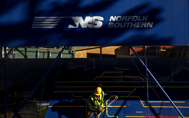 FILE- In this Oct. 23, 2019 file photo, a worker sweeps a sidewalk outside the construction site for the new corporate headquarters of Norfolk Southern Railway, in Atlanta. Norfolk Southern's third-quarter profit fell more than 13% as the railroad delivered fewer shipments and the results were weighed down by a one-time charge. The railroad said Wednesday, Oct. 28, 2020, that it earned $569 million, or $2.22 per share. (AP Photo/David Goldman, File)