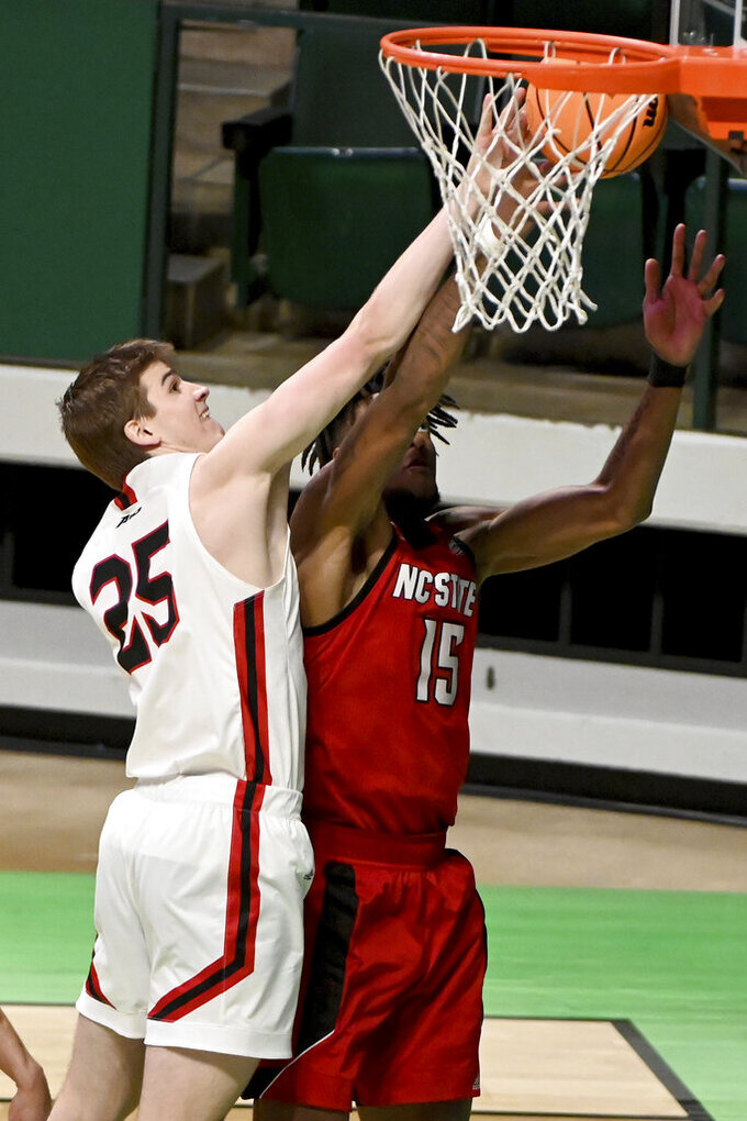 Davidson forward Bates Jones (25) goes after a rebound with North Carolina State forward Manny Bates (15) in the second half of an NCAA college basketball game in the first round of the NIT, Thursday, March 18, 2021, in Denton, Texas. North Carolina State won 75-61. (AP Photo/Matt Strasen)