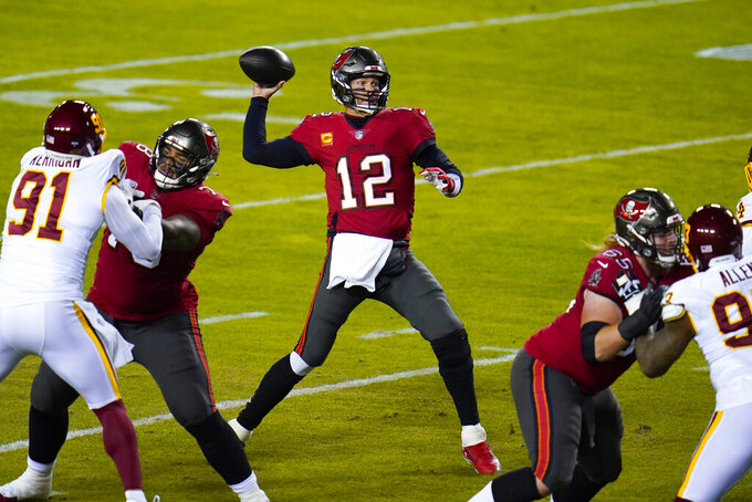 Tampa Bay Buccaneers quarterback Tom Brady (12) throwing the ball during the first half of an NFL wild-card playoff football game against the Washington Football Team, Saturday, Jan. 9, 2021, in Landover, Md. (AP Photo/Julio Cortez)