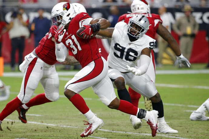 FILE - In this Aug. 15, 2019, file photo, Arizona Cardinals running back David Johnson (31) runs as Oakland Raiders defensive end Clelin Ferrell (96) defends during the first half of an an NFL preseason football game in Glendale, Ariz. The biggest issue last year in Oakland was the lack of a pass rush. The Raiders finished with just 13 sacks, 17 fewer than the second worst team. No. 4 overall pick Ferrell should help improve the rush a bit although much of his strength comes from his play against the run. Arden Key showed flashes as a rookie and could be more effective as a rusher in a more situational role and the interior rush should be improved with Maurice Hurst in his second year. (AP Photo/Rick Scuteri, File)