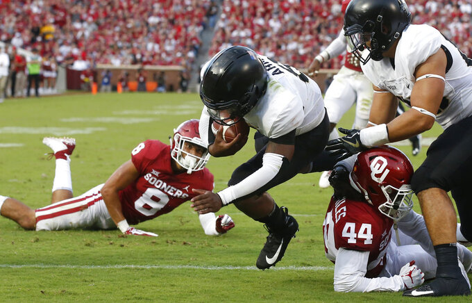 FILE - In this Saturday, Sept. 22, 2018, file photo, Army quarterback Kelvin Hopkins Jr. (8) scores between Oklahoma safety Kahlil Haughton (8) and defensive back Brendan Radley-Hiles (44) in the first half of an NCAA college football game in Norman, Okla. A year ago quarterback Hopkin knew he wasn't going to see much playing time under center for Army because starter Ahmad Bradshaw was having a stellar senior season for the Black Knights. Now, Hopkins is the lead man and has the demeanor he needs.(AP Photo/Sue Ogrocki)