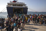 Refugees and migrants who just arrive at the port of Elefsina, near Athens, wait to board buses, on Tuesday, Oct. 22, 2019. About 700 refugees and migrants arrived from Samos island to the port of Elefsina as authorities have been moving hundreds of migrants deemed to be vulnerable from the overcrowded Samos camp to camps on the mainland. (AP Photo/Petros Giannakouris)