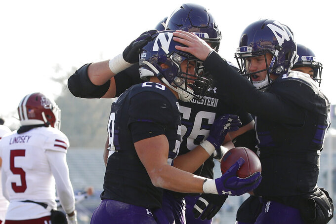 Northwestern's Tyler Haskin, second left, celebrates his touchdown with Aidan Smith, right, as Massachusetts's Donte Lindsey, left, walks off the field during the first half of an NCAA college football game Saturday, Nov. 16, 2019, in Evanston, Ill. (AP Photo/Jim Young)