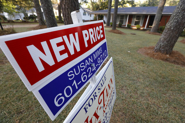 FILE - This Sept. 25, 2019, photo shows a sign indicating a new selling price for a house sits atop a realtor's sign in Jackson, Miss. On Tuesday, Dec. 31, the Standard & Poor's/Case-Shiller 20-city home price index for October is released. (AP Photo/Rogelio V. Solis)