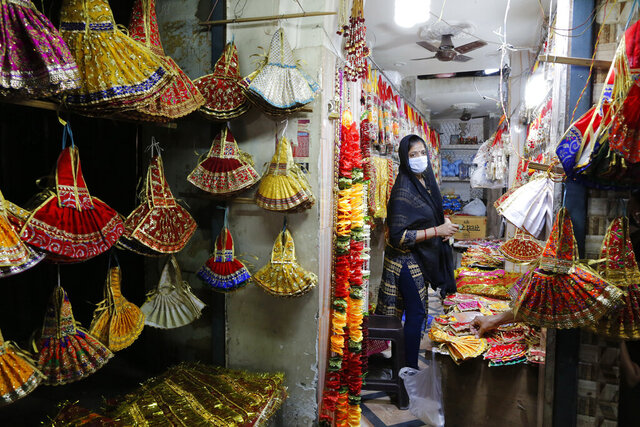 A Hindu woman wearing a mask shops for religious items on the eve of the Hindu festival Navratri in Prayagraj, India, Tuesday, March 24, 2020. Indian Prime Minister Narendra Modi Tuesday announced a total lockdown of the country of 1.3 billion people to contain the new coronavirus outbreak. For most people, the new coronavirus causes only mild or moderate symptoms. For some it can cause more severe illness. (AP Photo/Rajesh Kumar Singh)