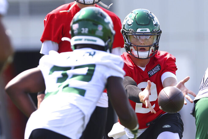 New York Jets quarterback Zach Wilson (2) pitches the ball to running back Michael Carter (32) during practice at the team's NFL football training facility, Saturday, July. 31, 2021, in Florham Park, N.J. (AP Photo/Rich Schultz)