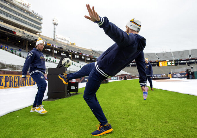 Nashville Predators' Ryan Johansen, left, and Mattias Ekholm, center, play with a soccer ball before the NHL Winter Classic hockey game against the Dallas Stars at the Cotton Bowl, Wednesday, Jan. 1, 2020, in Dallas. (AP Photo/Jeffrey McWhorter)