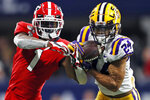 FILE - In this Dec. 7, 2019, file photo, LSU cornerback Derek Stingley Jr. (24) intercepts a pass intended for Georgia wide receiver George Pickens (1) during the second half of the Southeastern Conference championship NCAA college football game in Atlanta. (AP Photo/John Bazemore, File)