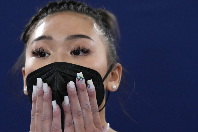 Sunisa Lee, of the United States, looks at the scoreboard for the final results of the artistic gymnastics women's all-around final at the 2020 Summer Olympics, Thursday, July 29, 2021, in Tokyo. (AP Photo/Gregory Bull)