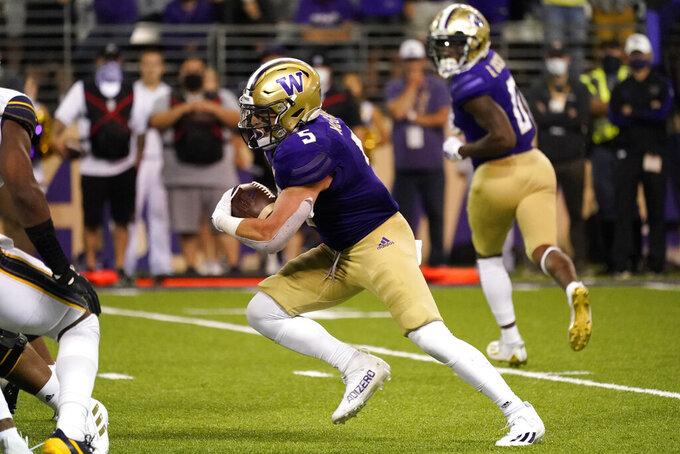 Washington's Sean McGrew (5) carries the ball against California in overtime in an NCAA college football game Saturday, Sept. 25, 2021, in Seattle. Washington won 31-24. (AP Photo/Elaine Thompson)