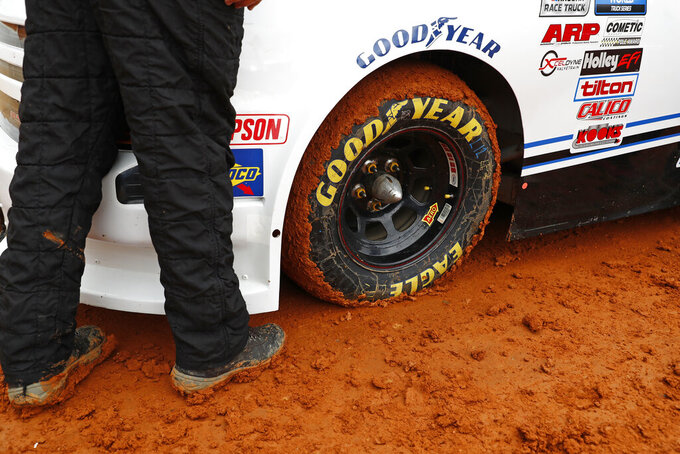 Mud stick to the tire of a truck as it prepares to compete in a heat race for a NASCAR Truck Series race on Saturday, March 27, 2021, in Bristol, Tenn. (AP Photo/Wade Payne)