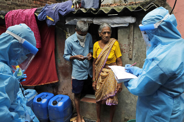 Health workers screen residents for COVID-19 symptoms at Deonar slum in Mumbai, India, Saturday, July 11, 2020. In just three weeks, India went from the world's sixth worst-affected country by the coronavirus to the third, according to a tally by Johns Hopkins University. India's fragile health system was bolstered during a stringent monthslong lockdown but could still be overwhelmed by an exponential rise in infections. (AP Photo/Rajanish Kakade)
