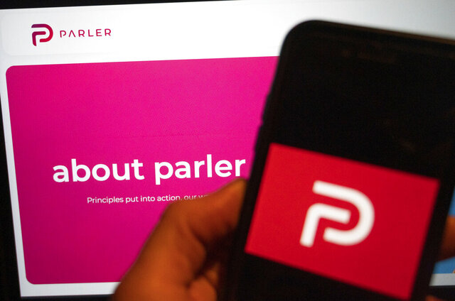 The logo of the social media platform Parler is displayed in Berlin, Jan. 10, 2021. In the background on a screen is the platform's website. The conservative-friendly social network Parler was booted off the internet Monday, Jan. 11, over ties to last week's siege on the U.S. Capitol, but not before hackers made off with an archive of its posts, including any that might have helped organize or document the riot. (Christophe Gateau/dpa via AP)