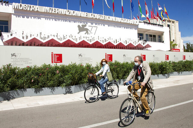Festival attendees cycle in front of the main cinema ahead of the start of the 77th edition of the Venice Film Festival in Venice, Italy, Tuesday, Sept. 1, 2020. Italy was among the countries hardest hit by the coronavirus pandemic, and the festival will serve as a celebration of its re-opening and a sign that the film world, largely on pause since March, is coming back as well. (Photo by Joel C Ryan/Invision/AP)