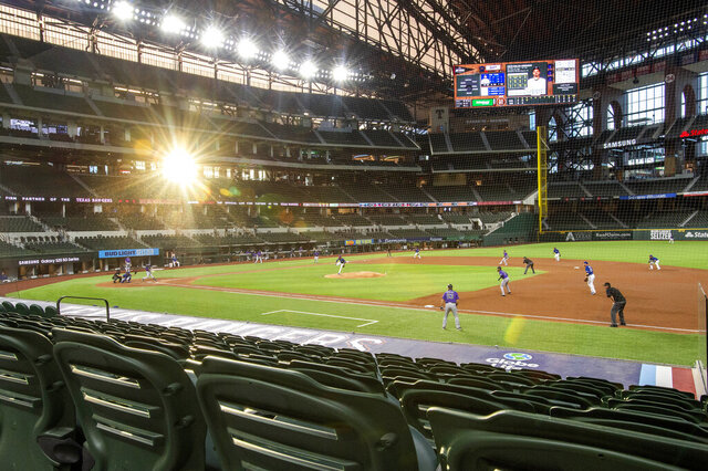 The setting sun shines through the windows of Globe Life Field during the third inning of a baseball game between the Texas Rangers and the Colorado Rockies Wednesday, July 22, 2020, in Arlington, Texas. (AP Photo/Jeffrey McWhorter)