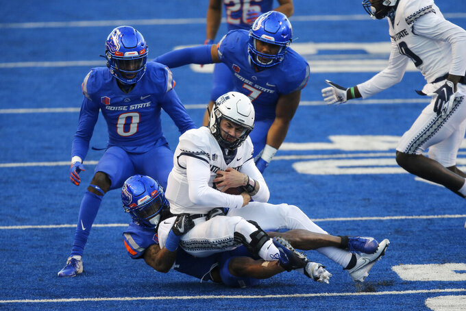 Utah State quarterback Andrew Peasley (6) is pulled to the ground by Boise State cornerback Jalen Walker (2) as teammates Boise State safety Jl Skinner (0) and Boise State linebacker Ezekiel Noa (7) close in during the first half of an NCAA college football game Saturday, Oct. 24, 2020, in Boise, Idaho. Boise State won 42-13. (AP Photo/Steve Conner)