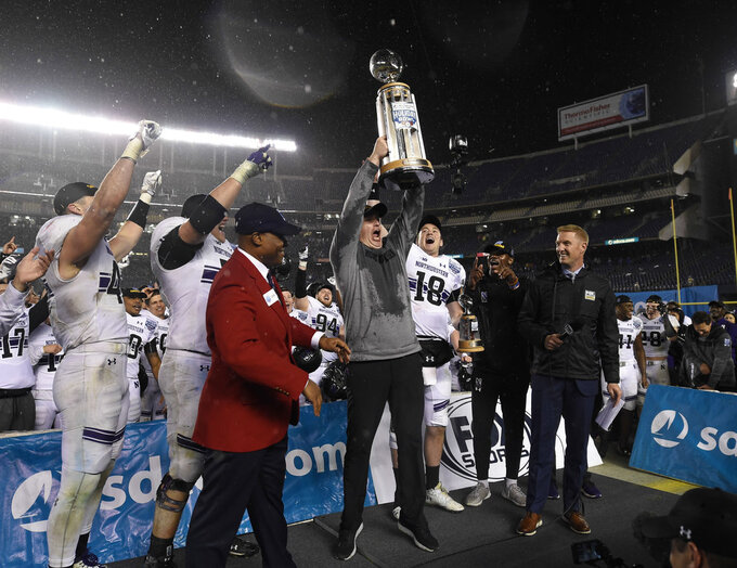 Northwestern head coach Pat Fitzgerald, center, lifts the Holiday Bowl trophy after defeating Utah in the Holiday Bowl NCAA college football game Monday, Dec. 31, 2018, in San Diego. (AP Photo/Denis Poroy)