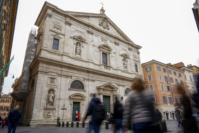 People walk past the St. Louis of the French church in Rome, Sunday, March 1, 2020. The French community church in Rome, St. Louis of the French, closed its doors to the public on Sunday, reportedly after a priest was infected with a new virus. The church in the historic center of Rome is famous for three paintings by the Baroque master Caravaggio, and is a tourist draw. A sign on the door Sunday noted in French that the church had been closed as a precaution by the French Embassy for both Masses and touristic visits until further notice. (AP Photo/Andrew Medichini)