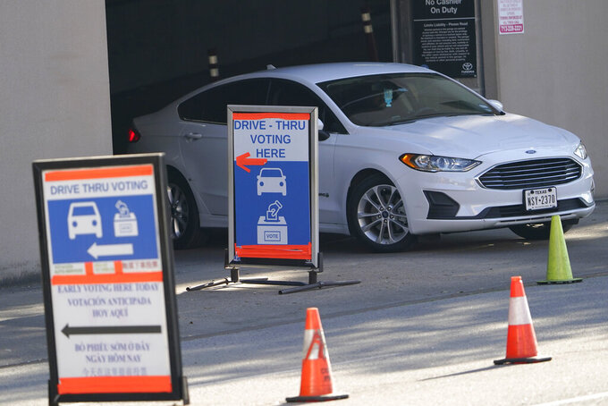 FILE - A car leaves a drive-thru voting site on Election Day on Nov. 3, 2020, in Houston. Texas has become the latest state where Republicans have rolled back access to voting methods that soared in popularity during last year's pandemic presidential election. Following similar legislation in Arizona, Florida, Georgia, Iowa and some other GOP-controlled states, Texas Republicans passed new restrictions on mail-in balloting as well as bans on 24-hour polling places and drive-thru voting.  (AP Photo/David J. Phillip, File)