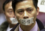 FILE - In this photo taken Friday, Feb. 14, 2003, demonstrators with tape over their mouth with the words