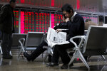 An investor reads a newspaper as others monitor stock prices at a brokerage house in Beijing, Friday, Dec. 6, 2019. Shares swung higher in Asia on Friday after a wobbly day of trading on Wall Street as investors awaited a U.S. government jobs report and kept an eye out for developments in China-U.S. trade talks. (AP Photo/Andy Wong)
