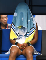Japan's Naomi Osaka sits with a towel over her head during a break in her second round match against China's Zheng Saisai at the Australian Open tennis championship in Melbourne, Australia, Wednesday, Jan. 22, 2020. (AP Photo/Andy Brownbill)