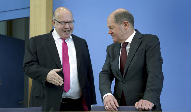FILE - In this March 23, 2020 file photo, German Economy Minister, Peter Altmaier, left, tries to shake hands with German Finance Minister Olaf Scholz, right, prior to a press conference in Berlin, Germany. From the U.S. president to the British prime minister's top aide and far beyond, leading officials around the world are refusing to wear masks or breaking confinement rules meant to protect their populations from the coronavirus and slow the pandemic. While some are punished when they're caught, or publicly repent, others shrug off the violations as if the rules don't apply to them. (AP Photo/Michael Sohn, pool, File)
