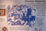 This image provided by Hinkle Fieldhouse shows a plaque hanging in Hinkle Fieldhouse in Indianapolis, Monday, May 4, 2020. The plaque tells the story of how the Milan High School basketball team won the 1954 Indiana state basketball championship, and features a group photo by team photographer William Crider. The team's thrilling run to the Indiana state title is the basis for the movie