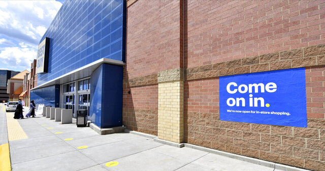 Shoppers, left, head to the entrance as a sign on the outside wall invites customers to shop inside a Best Buy store Wednesday, June 24, 2020 in Richfield, Minn. as restrictions due to the coronavirus have eased in Minnesota. (AP Photo/Jim Mone)