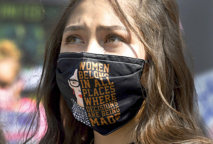 Hundreds protest on many issues including the Trump Administration's efforts to replace the late Supreme Court Justice Ruth Bader Ginsburg and asking people to get out and vote during the Los Angeles Women's March from Pershing Square to City Hall in Los Angeles on Saturday, Oct. 17, 2020. (Keith Birmingham/The Orange County Register via AP)