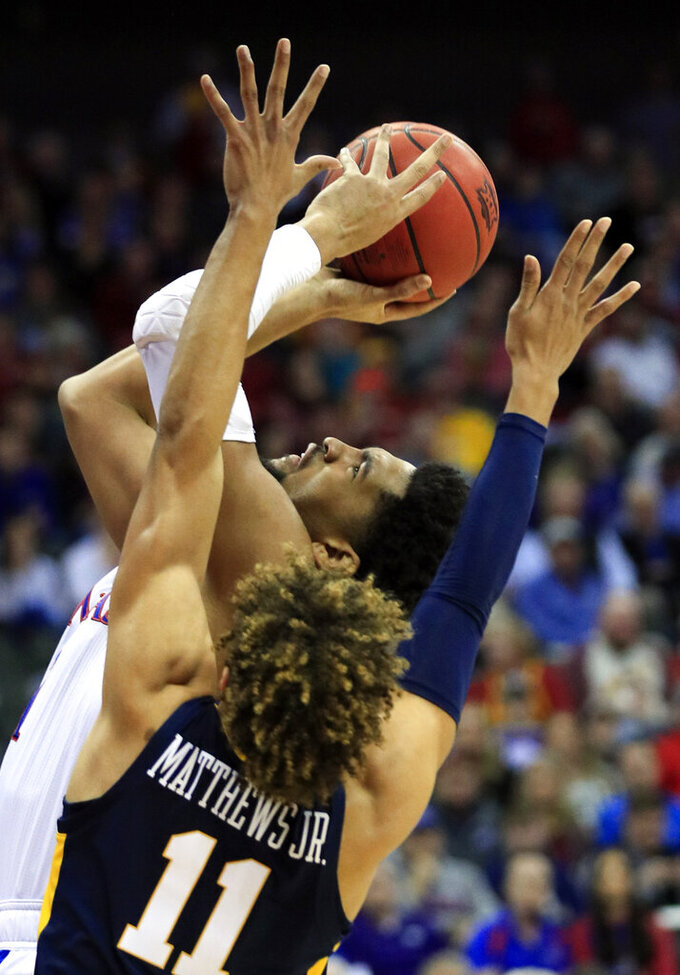 Kansas forward Dedric Lawson (1) shoots while covered by West Virginia forward Emmitt Matthews Jr. (11) during the first half of an NCAA college basketball game in the semifinals of the Big 12 conference tournament in Kansas City, Mo., Friday, March 15, 2019. (AP Photo/Orlin Wagner)