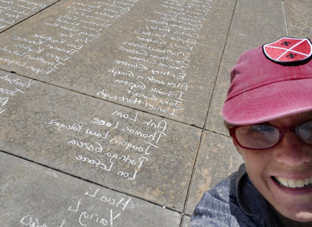 In this May 8, 2020 photo, Kim Gaddie, an Associate Senior Fellow at Headington College, takes a selfie photo of herself with a long list of University of Oklahoma graduate names written on the sidewalk outside of the Gaylord Family-Oklahoma Memorial Stadium in Norman, Okla.. Gaddie and several staff members spent hours writing more than 4,000 names of the 2020 graduates who were unable to have their in-person commencement ceremony due to COVID-19. (Courtesy of Kim Gaddie via AP)