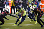 Seattle Seahawks running back Carlos Hyde (30) rushes as Arizona Cardinals free safety Jalen Thompson (34) attempts the tackle during the first half of an NFL football game, Thursday, Nov. 19, 2020, in Seattle. (AP Photo/Elaine Thompson)