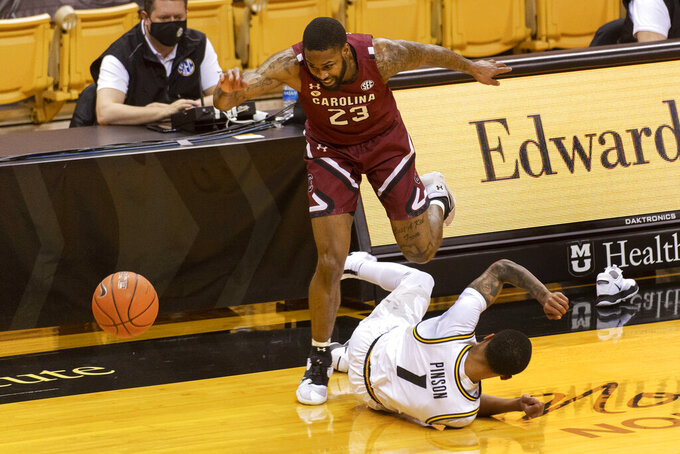 South Carolina's Seventh Woods hops over Missouri's Xavier Pinson, who lost a shoe during the first half of an NCAA college basketball game Tuesday, Jan. 19, 2021, in Columbia, Mo. (AP Photo/L.G. Patterson)