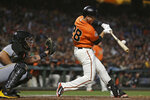 FILE - In this Aug. 10, 2018, file photo, San Francisco Giants' Buster Posey hits a two-run single off Pittsburgh Pirates starting pitcher Clay Holmes during the third inning of a baseball game, in San Francisco. Working out his lower body with a 15-pound dumbbell in his left hand he leaned forward to do a one-legged dead lift. Posey immediately felt the muscles in his right buttocks being used exactly the way they should. Posey certainly plans to be a full participant from Day 1 of spring training, pulling on the catcher's gear and squatting behind the plate for bullpens. (AP Photo/Eric Risberg, File)