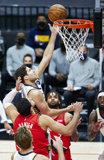 Indiana Pacers forward Doug McDermott, center, shoots between Portland Trail Blazers center Enes Kanter, left, and guard Gary Trent Jr. during the first half of an NBA basketball game in Portland, Ore., Thursday, Jan. 14, 2021. (AP Photo/Craig Mitchelldyer)