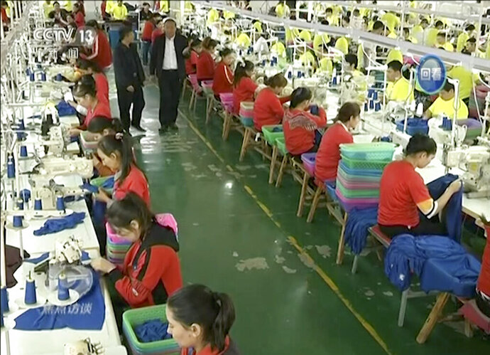 FILE - In this file image from undated video footage run by China's CCTV via AP Video, Muslim trainees work in a garment factory at the Hotan Vocational Education and Training Center in Hotan, Xinjiang, northwest China. A U.S. company that stocks college bookstores with t-shirts and other team apparel cut ties Wednesday, Jan. 9, 2019, with a Chinese company that drew workers from an internment camp holding targeted members of ethnic minority groups. (CCTV via AP Video, File)