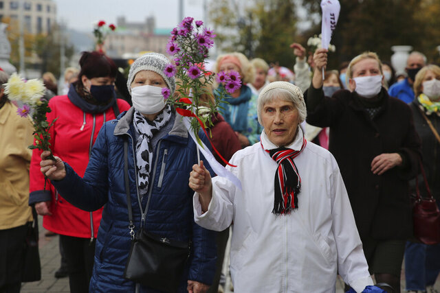 Elderly women hold flowers during an opposition rally to protest the official presidential election results in Minsk, Belarus, Monday, Oct. 12, 2020. Riot police clashed with protesting pensioners in central Minsk on Monday. The pensioners marched in a column through central Minsk, carrying flowers and posters with slogans such as