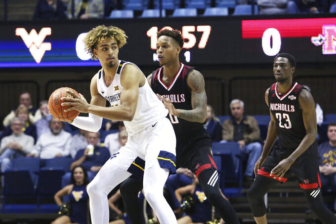West Virginia forward Derek Culver (1) goes to pass the ball as he is defended by Nicholls State guard D'Angelo Hunter (0) and forward Elvis Harvey Jr. (23)  during the first half of an NCAA college basketball game Saturday, Dec. 14, 2019, in Morgantown, W.Va. (AP Photo/Kathleen Batten)