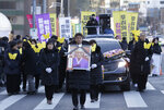 A mourner with a portrait of the deceased Kim Bok-dong, a former South Korean sex slave, marches toward the Japanese Embassy during her funeral ceremony in Seoul, South Korea, Friday, Feb. 1, 2019. Hundreds of mourners gathered Friday near the embassy for the funeral of Kim forced as a girl into a brothel and sexually enslaved by the Japanese military in WWII. (AP Photo/Ahn Young-joon)