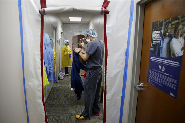 Dr. Drew Miller, front, and other medical staff suit up in protective gear as they prepare to check potential COVID-19 patients Wednesday, May 20, 2020 in a makeshift isolation area at Kearny County Hospital in Lakin, Kan. The rural 24-bed hospital is currently treating five patients inpatient for COVID-19 as the county has seen a spike in cases due to clusters in nearby meatpacking plants. (AP Photo/Charlie Riedel)