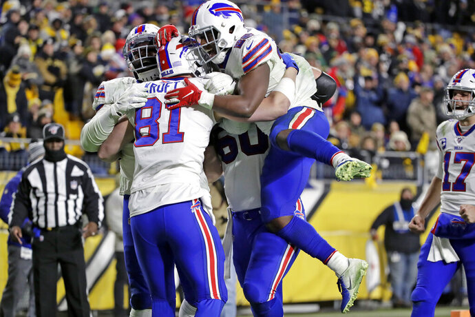 Buffalo Bills tight end Tyler Kroft (81) celebrates with running back Devin Singletary (26) and others after scoring on a pass from quarterback Josh Allen during the second half of an NFL football game against the Pittsburgh Steelers in Pittsburgh, Sunday, Dec. 15, 2019. (AP Photo/Don Wright)