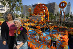 Ofelia Esparza, 88, with her daughter, Rosanna Esparza Ahrens, left, from East Los Angeles, stand Thursday, Oct. 29, 2020, by their community altar titled