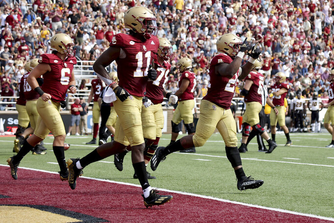 Boston College running back Pat Garwo III (24) celebrates with teammates as he heads to the sideline after scoring a touchdown during the second half of an NCAA college football game against Missouri, Saturday, Sept. 25, 2021, in Boston. (AP Photo/Mary Schwalm)